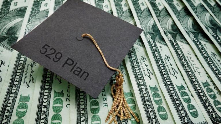 graduation hat on dollars with 529 plan writing