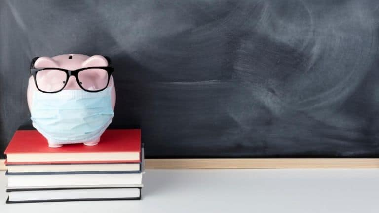 piggy bank on top of book infront of board