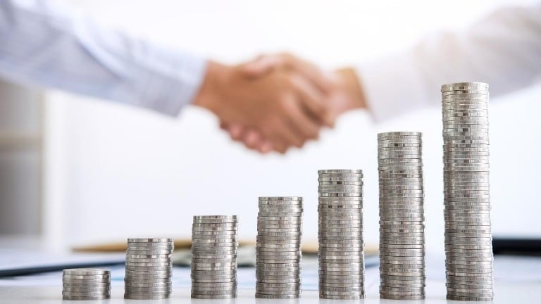 handshake investment stacking coins