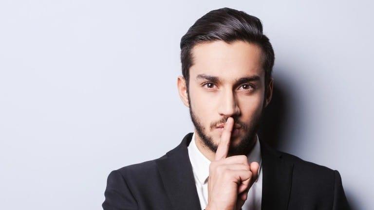 man signaling to keep a secret